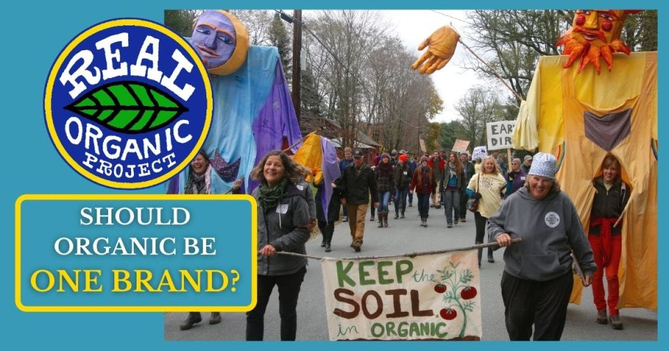 """A parade of farmers with large puppets at the front. Two women carry a banner reading """"Keep The Soil In Organic"""""""