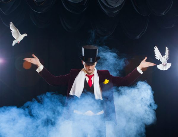 A magician in a tuxedo wears a top hat and a white scarf is surrounded by smoke while releasing two white doves