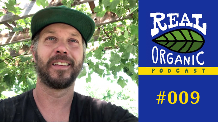 Jean Martin Fortier smiles at the camera with tree branches and leaves in the background. A blue box with the Real Organic Podcast logo and yellow lettering #009