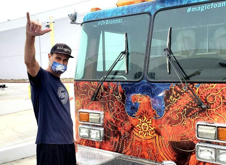 """David Bronner wears a face mask and holds his right hand up in a """"hang loose"""" signal with a multicolored firetruck."""