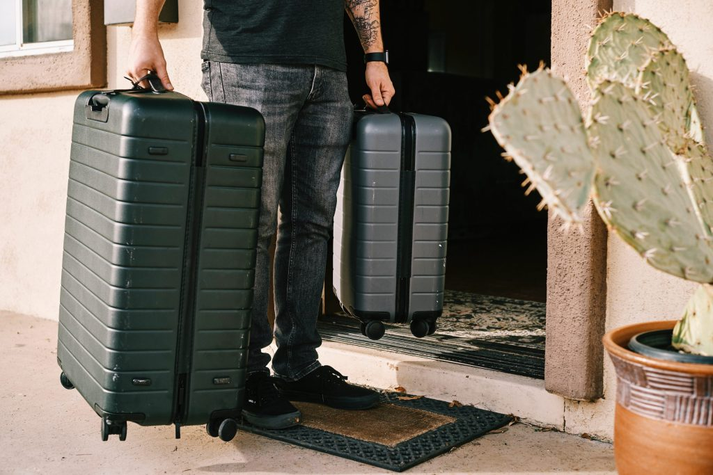 Man lifting two carry-on luggage bags into the front entry of a home