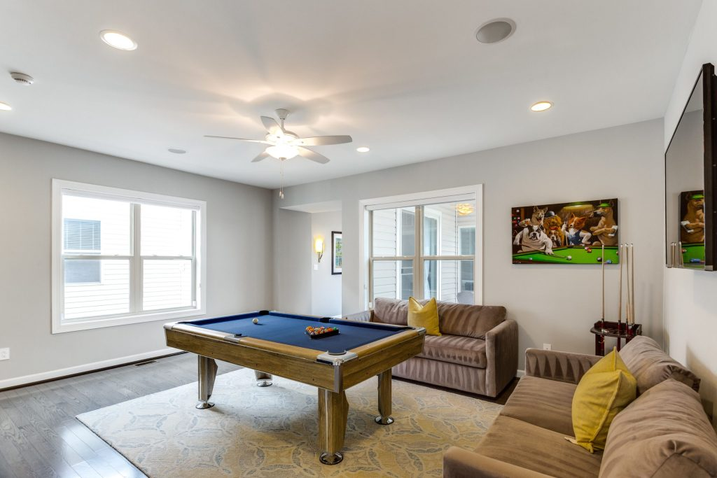 View of the pool table, painting of dogs playing pool, couches and television