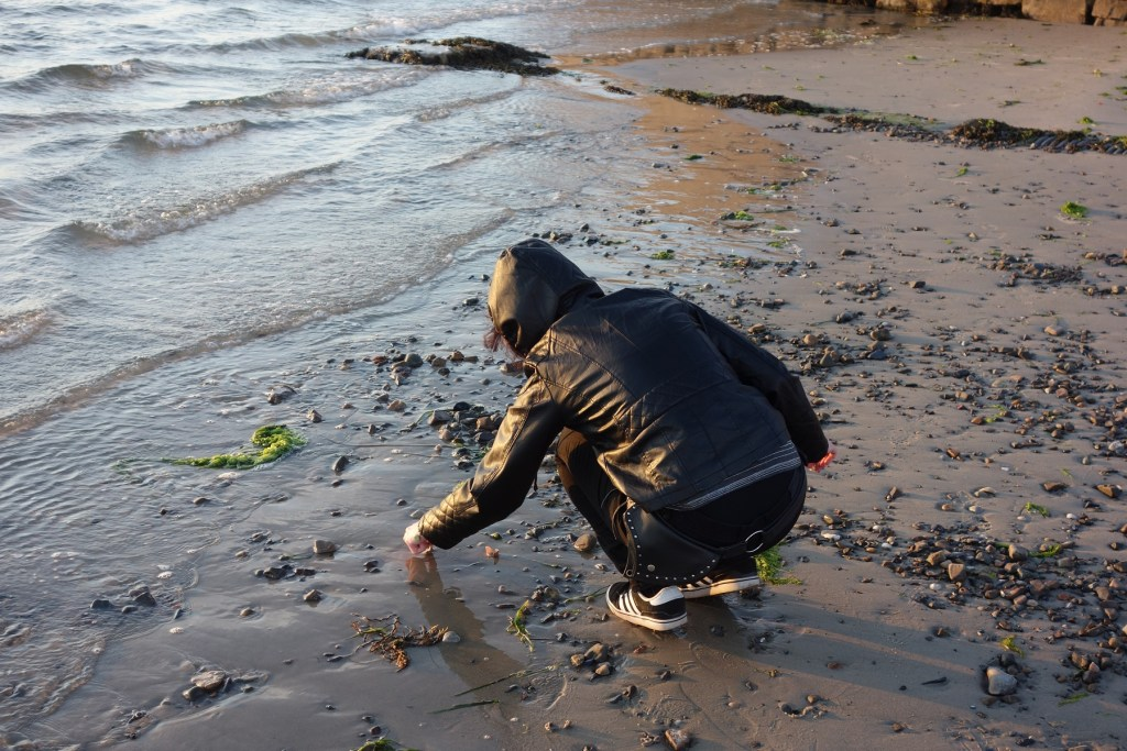 girl in leather jacket, on beach, facing away from camera, picking something off the sand near the water's edge