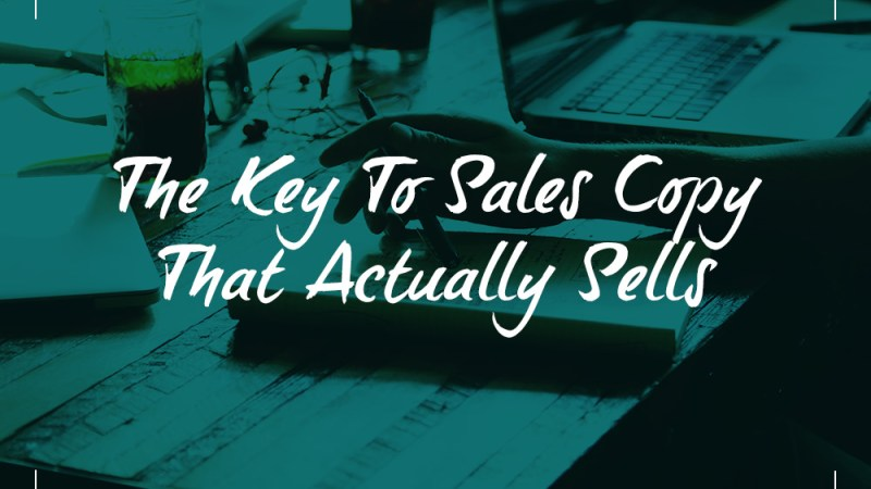 a desk covered in papers, laptop, drinks and more with the caption: The Key To Sales Copy That Actually Sells