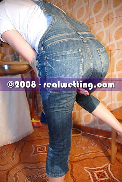 Teenager Alice is pissing herself in jeans overalls