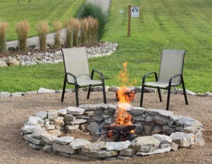 Stacked Stone Fire Pit in the middle of two chairs outdoors