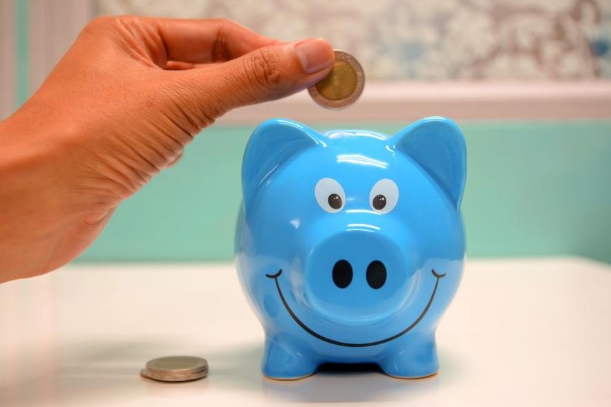 person putting coin inside blue piggybank