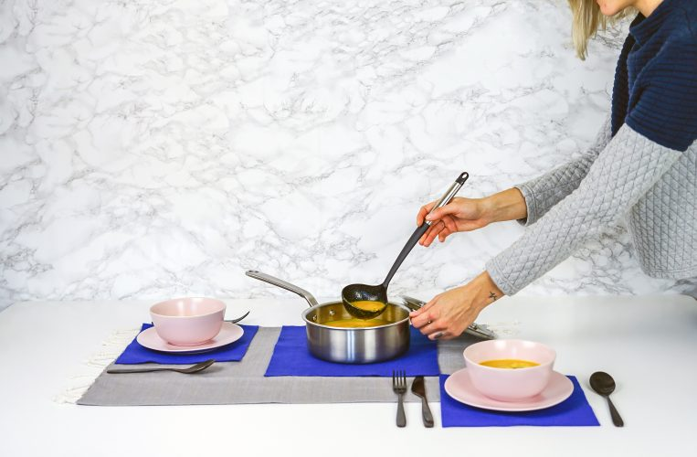 a woman pouring the pumpkin soup from the pot into a bowl