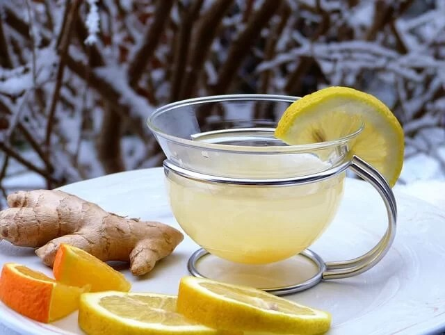 A warm cup of lemon and ginger herbal tea on a table on a frozen and snowing winter day.
