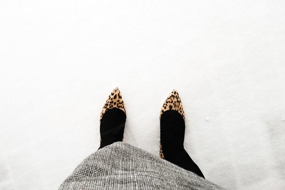 Image of Rebecca standing in a snowstorm in heels.