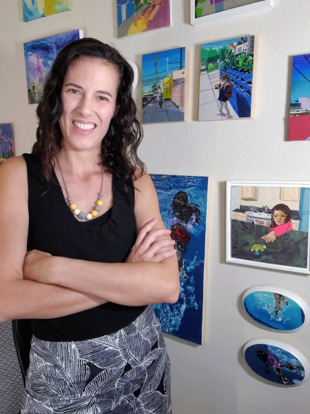 Rebecca Potts Aguirre standing in front of her artwork.