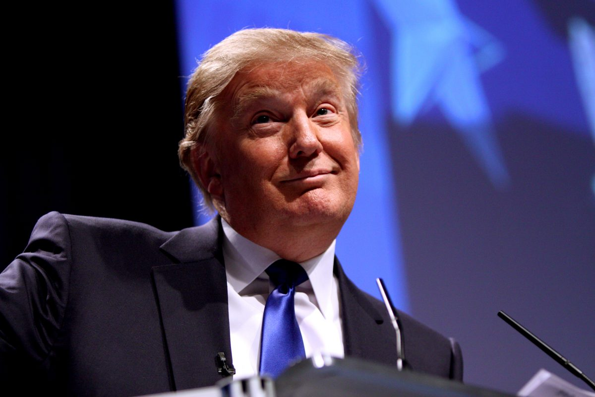 Donald Trump sits smirking, in front of microphones, wearing a suit and a blue tie.