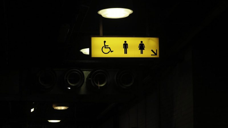 A dim street, with a bright yellow sign hanging above, displaying the symbols for disabled, male, and female toilet facilities.