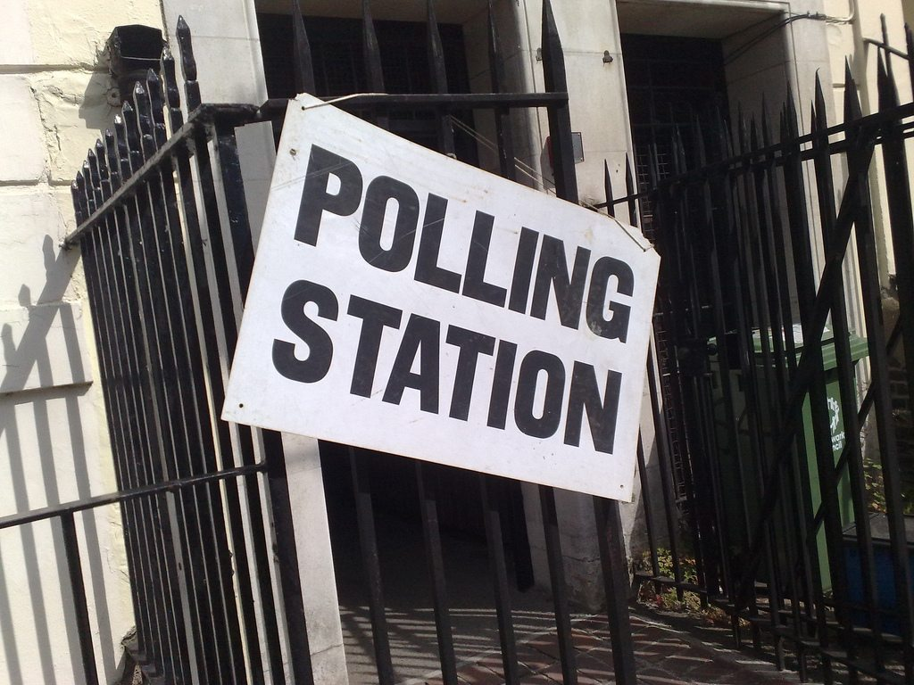 """Black railings outside of a white building, with a white """"Polling Station"""" sign hung on the fence."""