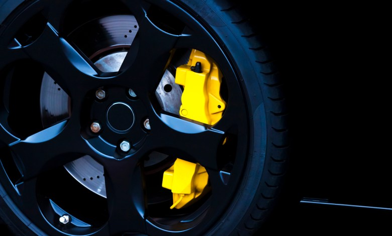 Black alloy wheel with yellow carbon ceramic brake, copy space