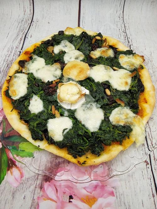 Plato de pizza de espinacas con queso de cabra, pasas y piñones
