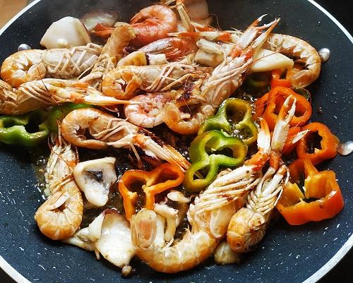 Ingredientes que se van añadiendo para la preparación de la paella marinera o de marisco