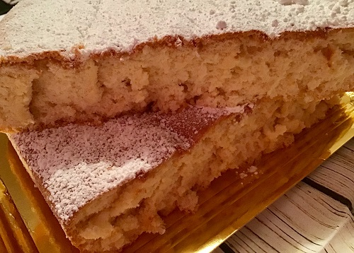 Bizcocho de pa de pessic cortado por la mitad y espolvoreado con azúcar glas.