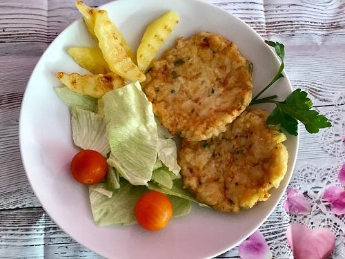 Un plato con 2 hamburguesas de rape caseras, ensalada y patatas fritas.