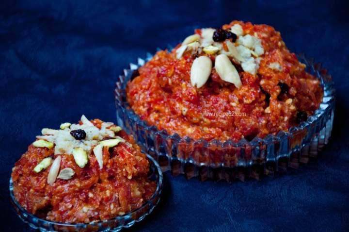 gajar ka halwa served in a dish and garnished with nuts.