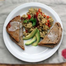overhead shot of curry scrambled eggs with buttered toast and slices of avocado