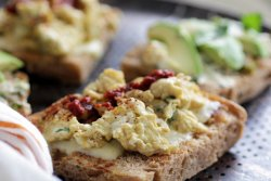 close up of cheese and scrambled eggs on toasted whole wheat focaccia bread