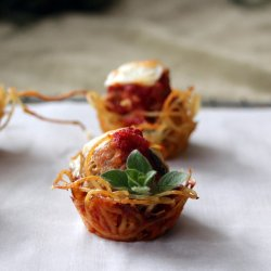 close up of an individual spaghetti and meatball bite on parchment paper, garnished with a spring of fresh oregano