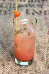 gin and pink grapefruit cocktail in a tall glass sitting on a burlap surface and garnished with tiny thyme leaves and a twist of grapefruit