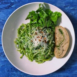fettuccini noodles dressed with bright green pesto, topped with grated parmesan and served with a slice of ciabatta and green salad