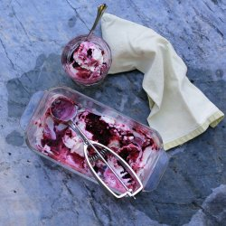a glass loaf pan filled with partially scooped out cheesecake ice-cream swirled with dark purple black raspberries