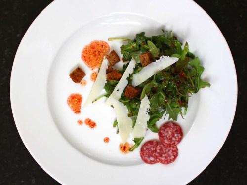 arugula salad with cranberry pomegranate dressing, homemade croutons, and shaved pecorino romano