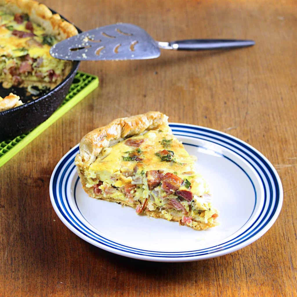 a big old slice of cast iron quiche w/ ham and sharp cheddar cheese