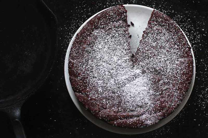 overhead shot of brown butter flourless chocolate cake dusted with powdered sugar