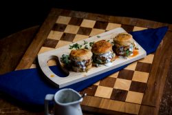 Three Buffalo Biscuit Sliders with buttermilk blue cheese dressing on a light wooden cutting board and wooden chess board with a blue napkin