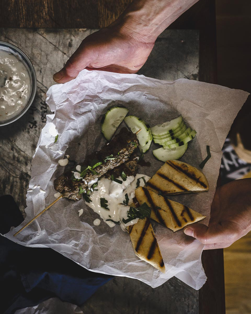 Holding a plate of Kofta-esque: ground beef kebabs with yogurt dipping sauce
