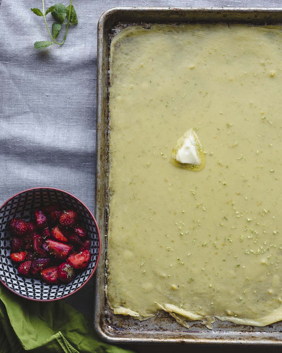 Sheet Pan Swedish Pancakes with fresh strawberries and lime just out of the oven