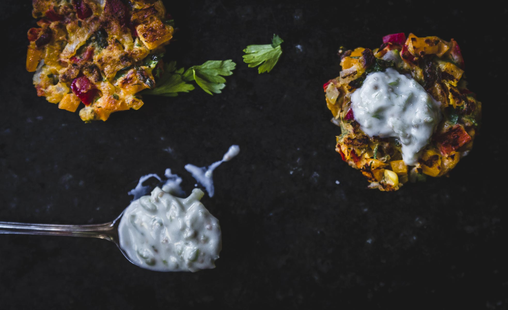 Tomatillo Tzatziki served on a red pepper summer vegetable fritter
