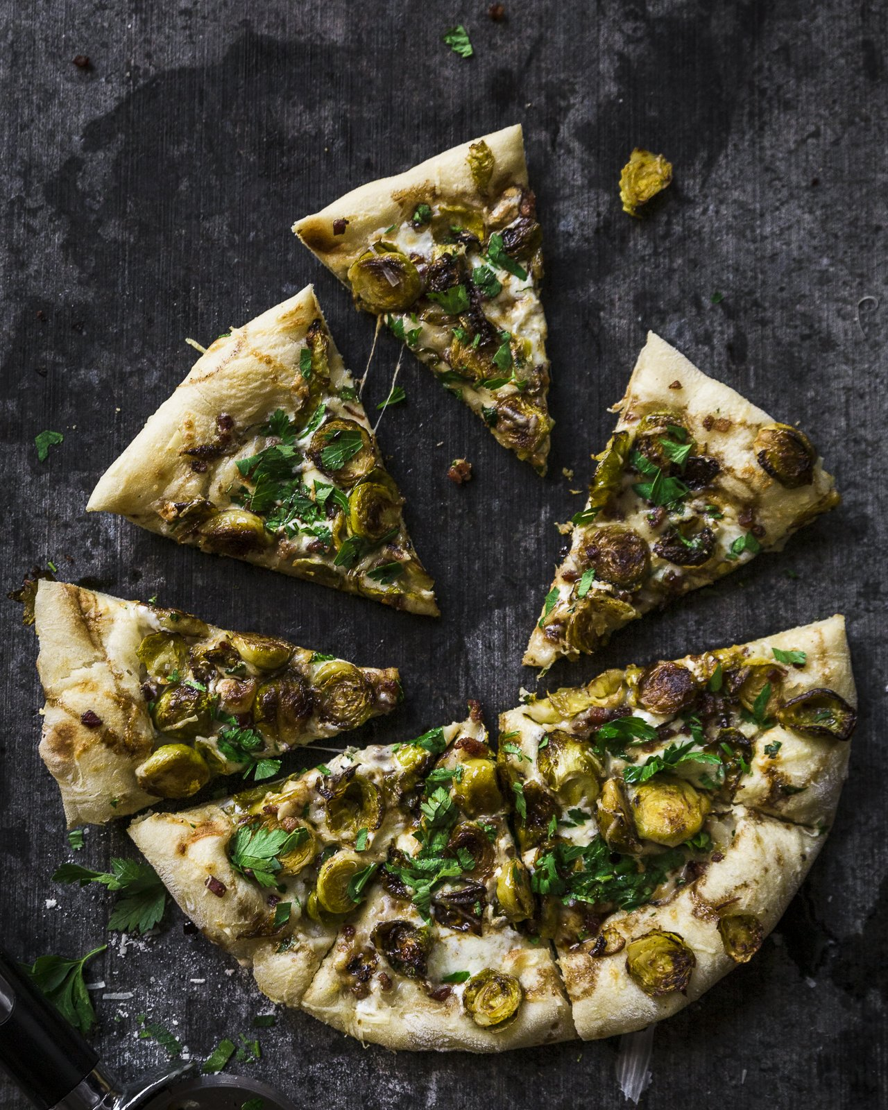 cast iron brussel sprout pizza sliced and ready to eat