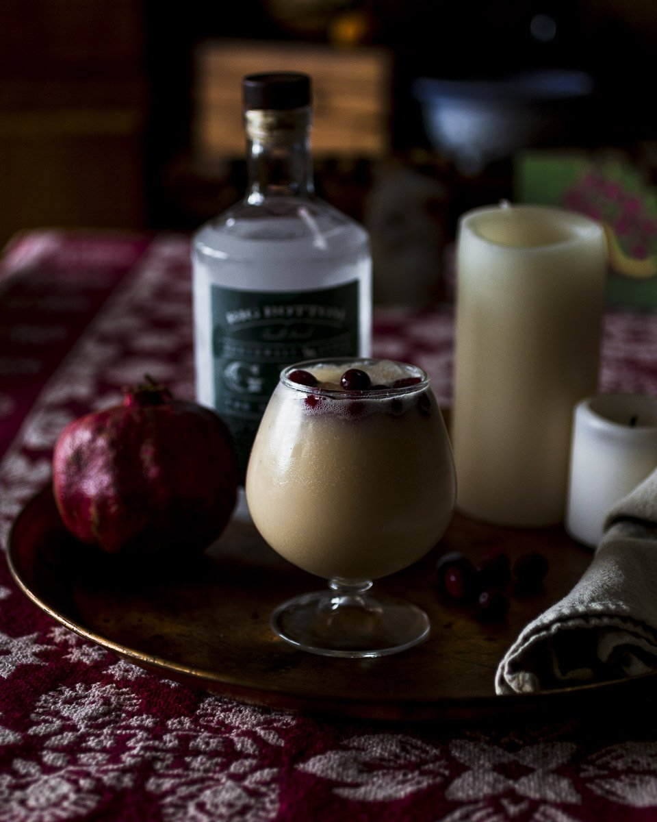 eggnog gin fizz cocktail with cranberry garnish