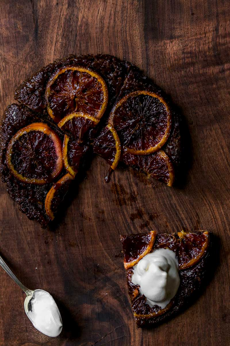 overhead shot of Upside-down Caramelized Orange Chocolate Tart topped with whipped cream on a wooden board