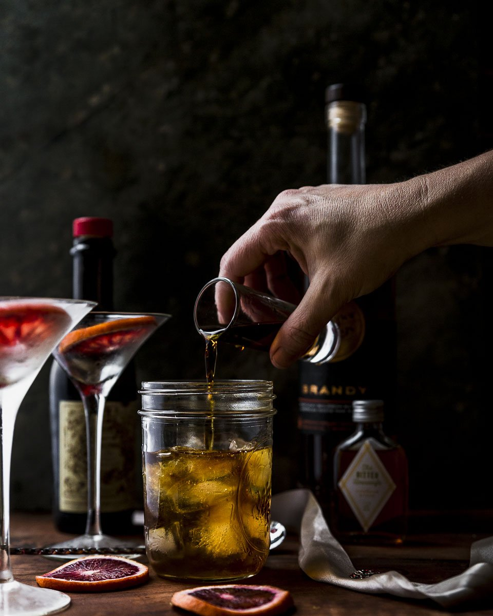 pouring the sweet vermouth into the brandy manhattan cocktail