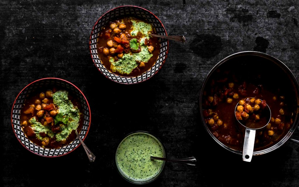Chickpea Chili with spicy cilantro cream overhead shot with bowls and side