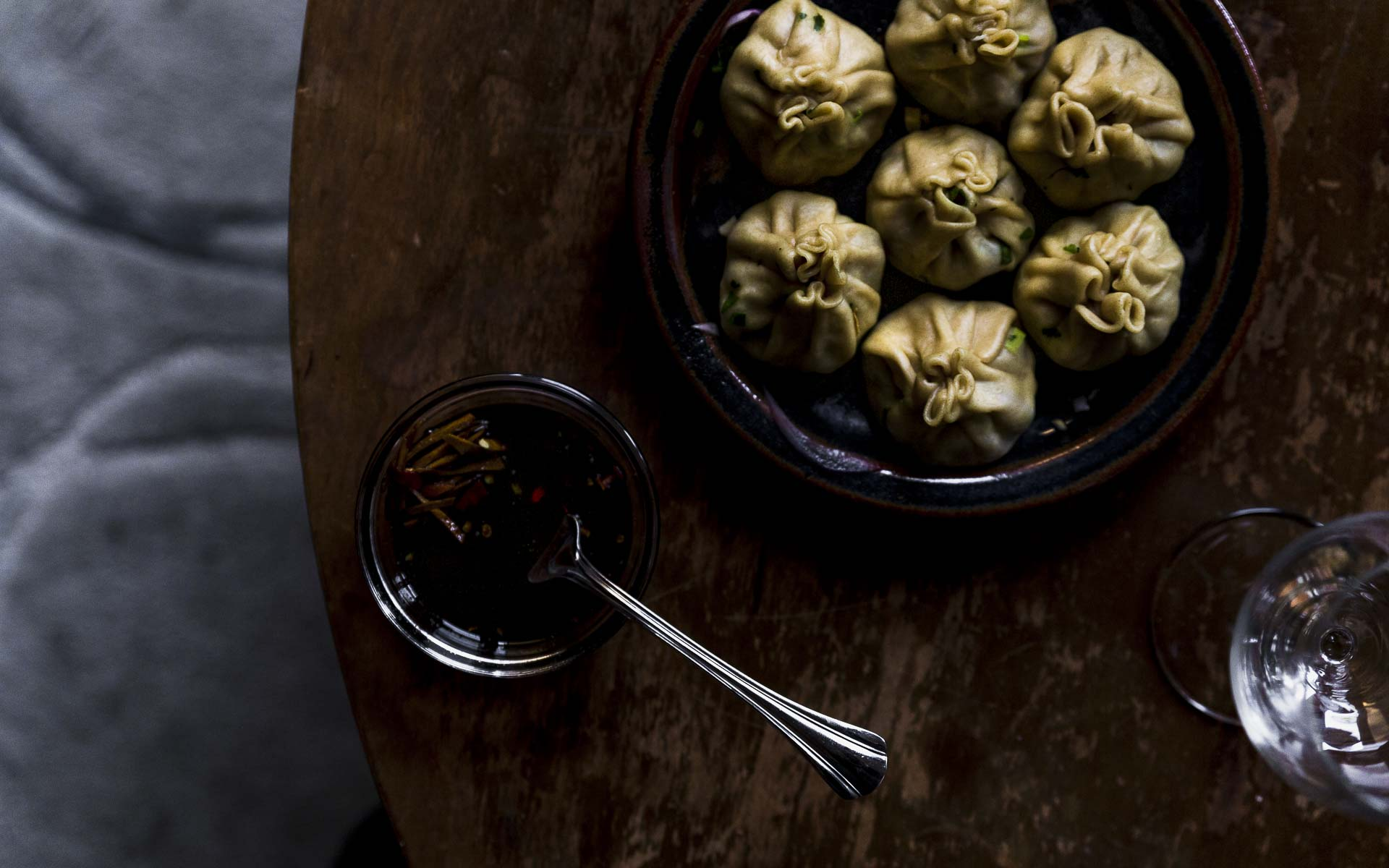close up of steamed lamb dumplings with soy vinegar dipping sauce