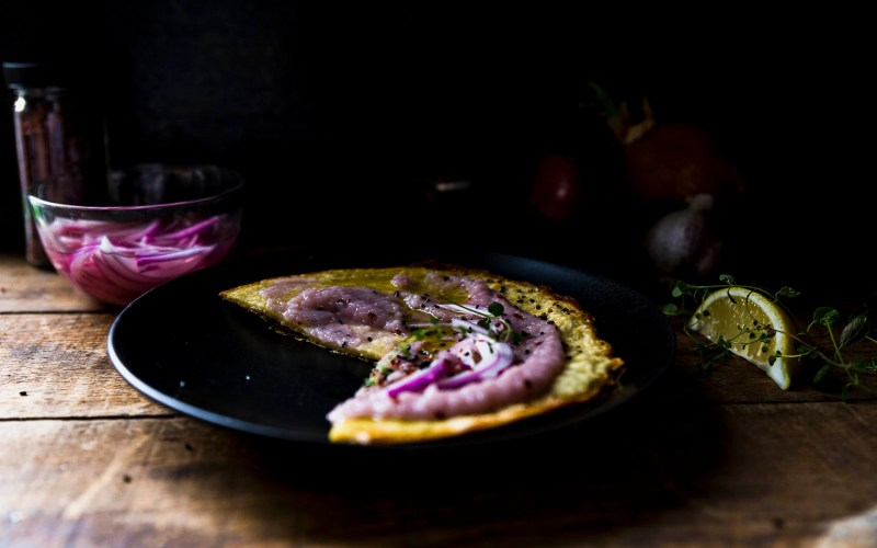 Side view of Socca- chickpea flour flatbread on a black plate