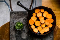 spicy sweet potatoes roasted in cast iron and served with cilantro sauce