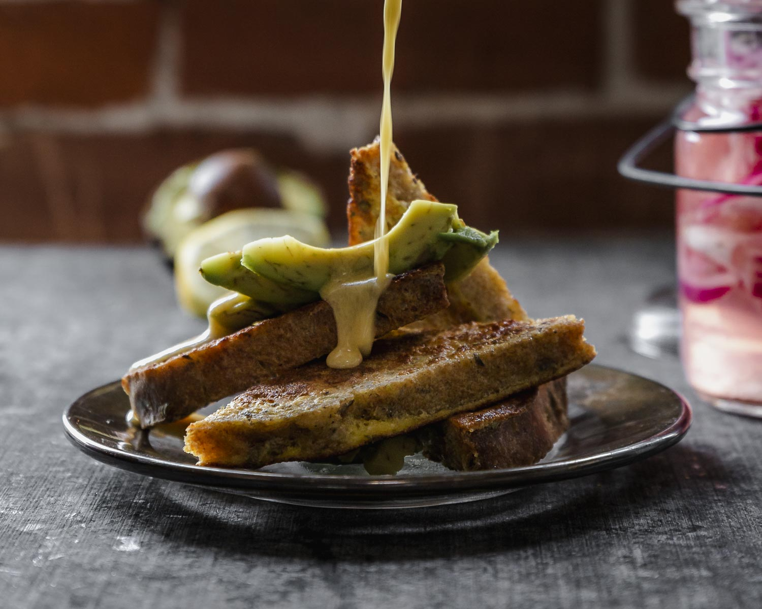 close up ofpouring the hollandaise over savory french toast with avocado
