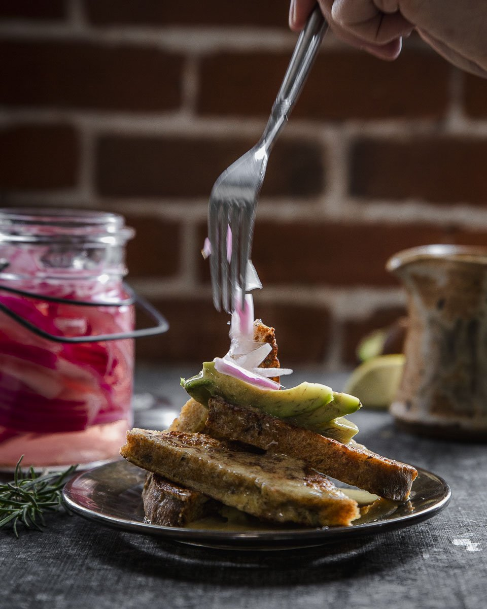 putting the pickled onions on the savory herb french toast with hollandaise sauce