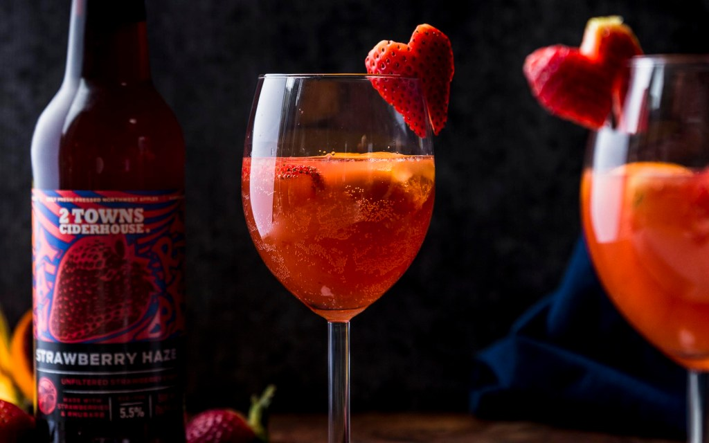 side view of two glasses of strawberry hard cider sangria with heart shaped strawberry garnish