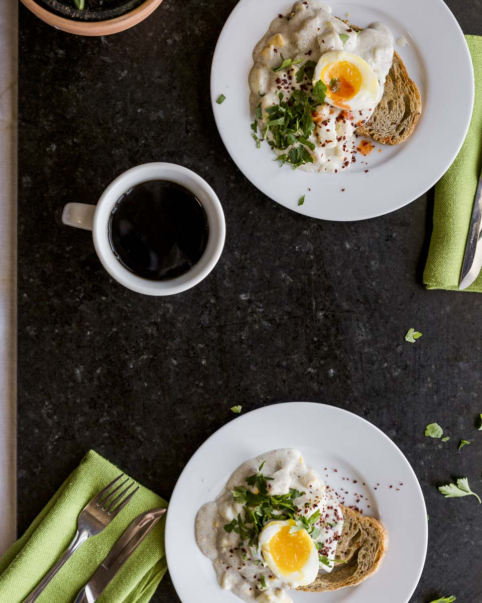 overhead shot of two plates of creamed eggs on toast with poached egg