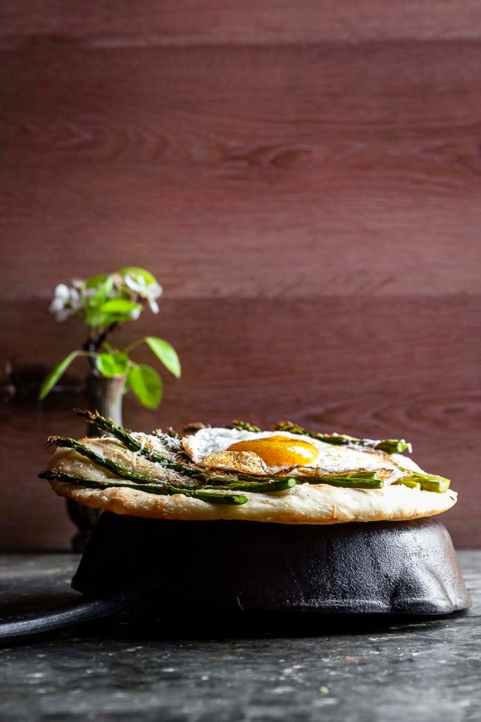 Easy Asparagus Flatbread topped with an egg and sitting atop a cast iron skillet